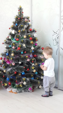 сыночек помогает наряжать елочку))